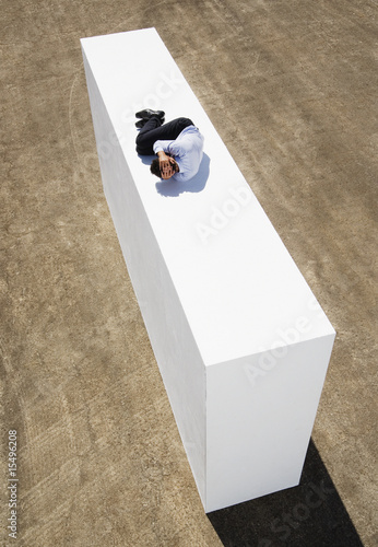 Businessman on wall outdoors in foetal position