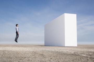 Man facing wall and jumping outdoors