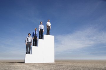 Four businesspeople standing on steps outdoors
