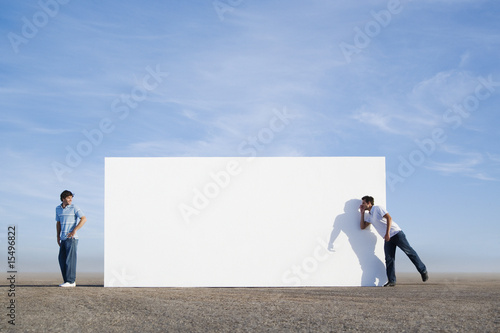 Two men outdoors with wall