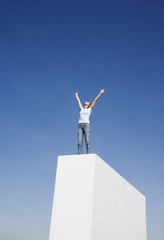 Woman standing on wall outdoors with arms up