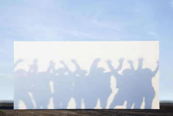 Silhouette shadows of people on a billboard