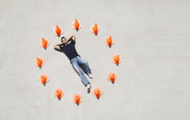 Man lying down in circle of traffic cones with arms up