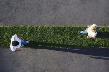 Woman and man walking on grass strip with pavement