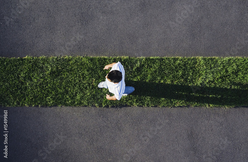 Man walking on grass strip with pavement