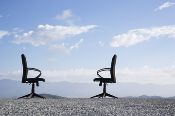 Two office chairs on a terrain full of pebbles