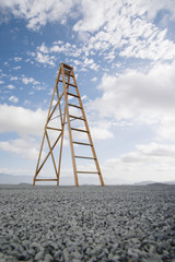 Ladder outdoors ground level view with blue sky and clouds