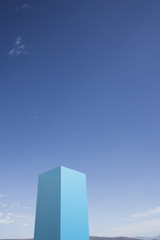 Blue cube set against sky