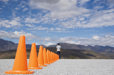 Man standing at the end of a row of safety cones