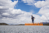Man standing by and looking down at a row of safety cones