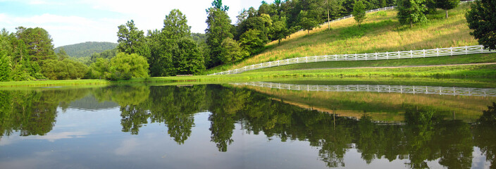 Attractive white horse fence and reflection in the trout pond