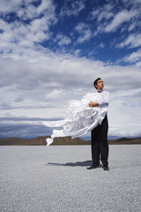 Man holding a bunch of papers in the wind
