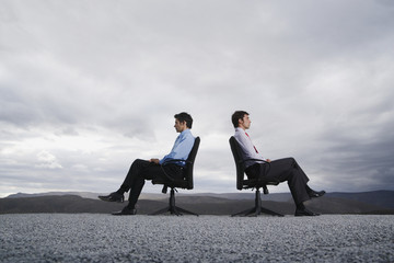 Two men sitting in office chairs outdoors with their backs against one another