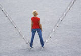 Woman standing outdoors on two ladders