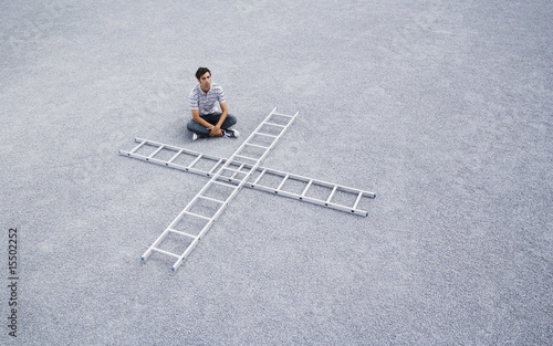 Man sitting cross legged outdoors with two ladders