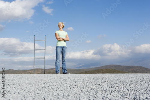 Woman standing outdoors with arms crossed and ladder