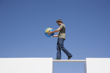 Man walking across plank with globe outdoors
