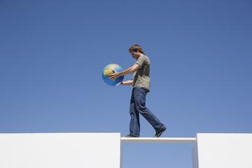 Man walking across plank with globe outdoors