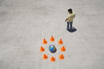 Man looking back at circle of safety cones with globe in center