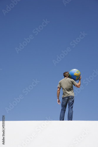 Rear view of man holding globe on shoulder outdoors