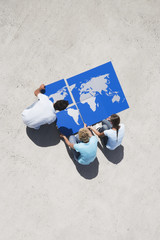 Aerial View of three people with pieces of world map puzzle outdoors