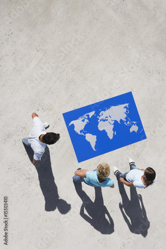 Aerial View of three people looking at world map puzzle outdoors