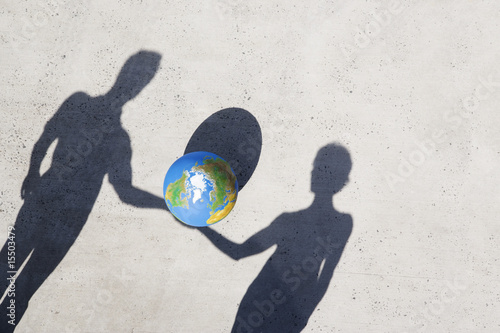 Aerial View of two shadows holding globe outdoors