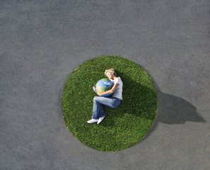 Woman lying down on circle of grass on pavement with globe