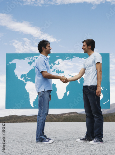 Two men shaking hands in front of world map outdoors