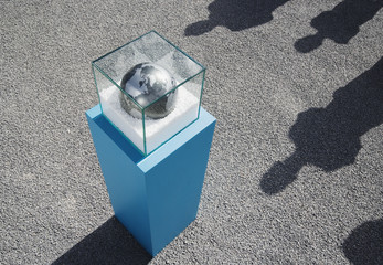 Globe in glass box on pedestal with four long shadows outdoors