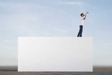 Man standing on wall outdoors with megaphone