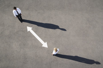 Aerial view of man and woman with arrow on pavement
