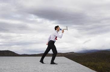 Businessman with megaphone outdoors shouting
