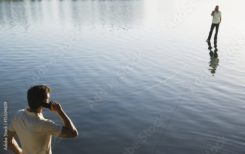 Two men standing on water with phone receivers and long cord