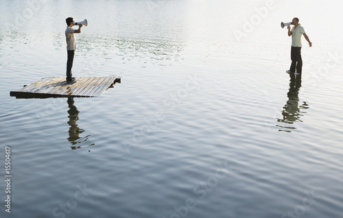Two men standing on water with megaphones