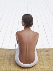 Woman sitting outdoors on a wicker mattress