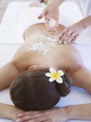 Masseuse applying massage salts to a woman's back
