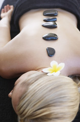 Woman with massage stones on her back
