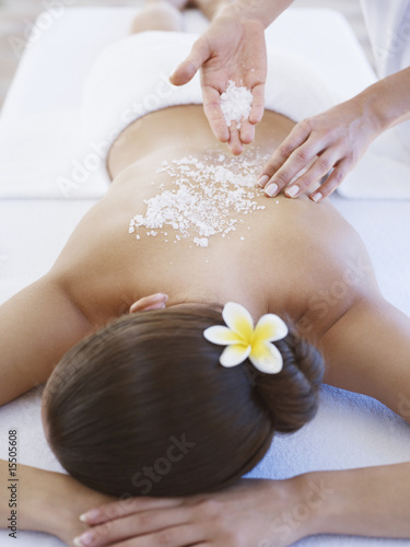 Masseuse applying massage salts to a woman's back