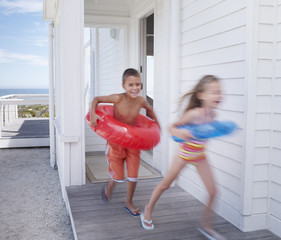 Two young kids leaving a beach house with swimming gear