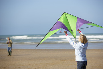 a couple flying a kite at the beach