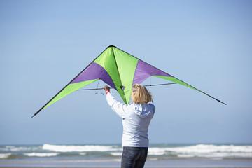 a senior woman with a kite at the beach