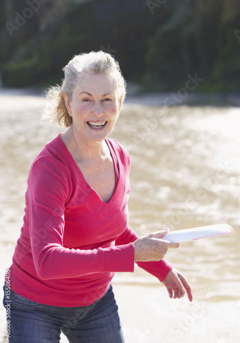 senior woman throwing a frisbee on the beach