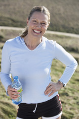 mature woman with a bottle of water resting after a jog