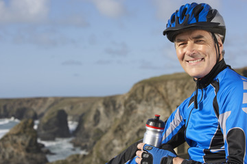 man in biking gear with a bottle of water