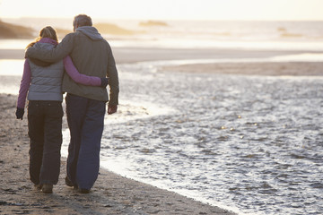 couple happily embracing walking down the beach