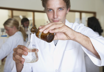 Man in a busy laboratory measuring liquids
