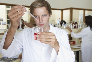 Man in a laboratory measuring liquids with an eyedropper