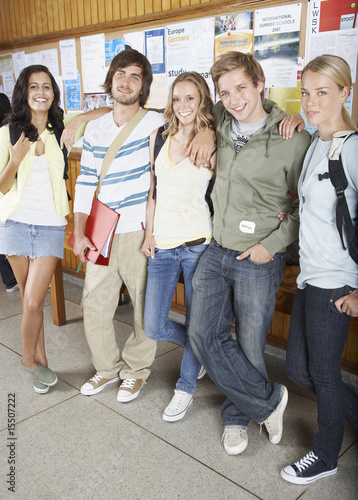 Five people in front of a bulletin board