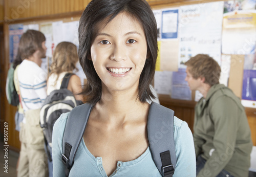 Woman in front of a bulletin board with people in the background